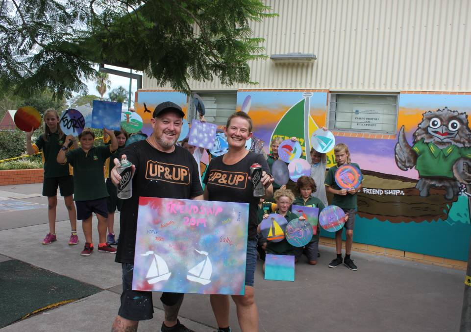 POSITIVE BEHAVIOUR: Up&Up Co-creators Shane Kennedy and Faith Curtis with the students, their own original artworks and the bright new mural.